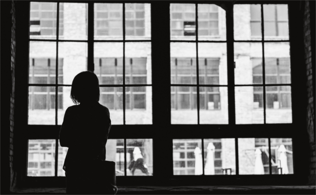 Silhoutte of person standing in front of window looking out onto street - social amxiety disorder - Bolton CBT, Emma Yarwood