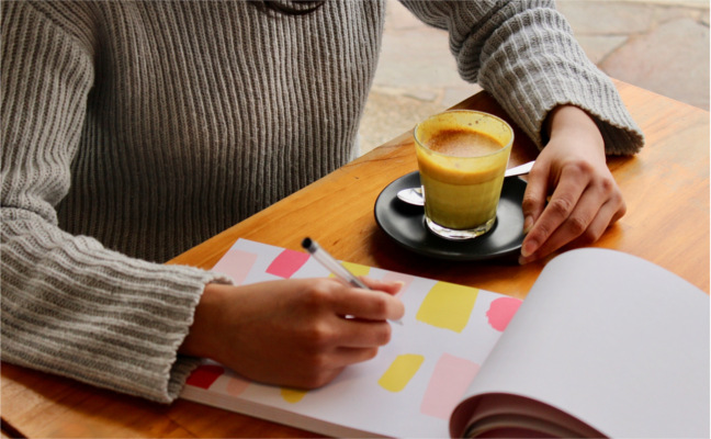 Close-up crop of woman at a table with coffee and notepad with colour swatches - low self esteem- Bolton CBT Emma Yarwood